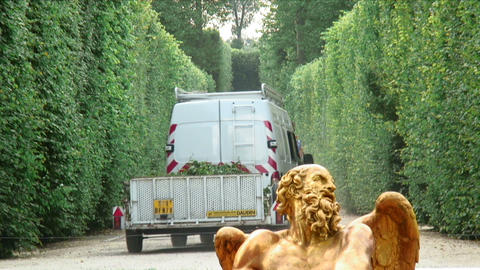 Van and trailer with branches between hedges in a garden with a statue Footage