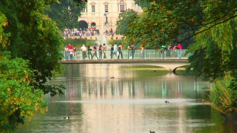 People on a bridge spanning a pond with a fountain Footage