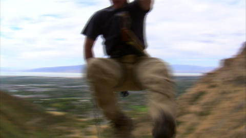 Clip of a mountain climber jumping over the camera Footage