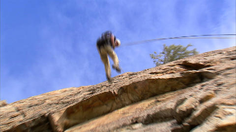Shot of a mountain climber rappelling down a cliff Footage