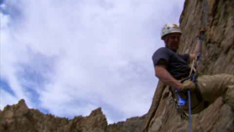 Mountain climber rappelling down a cliff Footage