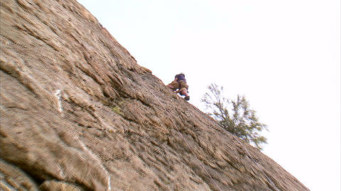 Shot of a rock climber rappelling down a cliff Footage