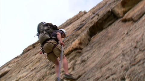 Clip of a rock climber rappelling down a cliff Footage