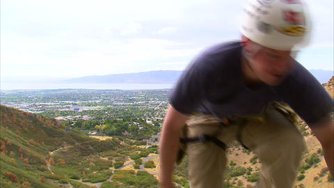 Rock climber coming over the top edge of a cliff Footage