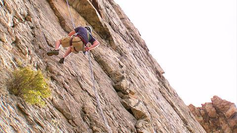 Shot of a rock climber jumping across a cliff face Footage