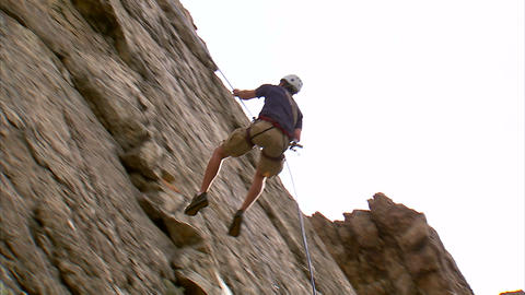 Clip of a rock climber jumping across a cliff face Footage