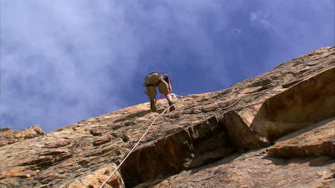 Clip of a rock climber climbing up a cliff Footage