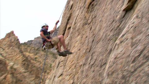 Rock climber hopping across a cliff face Live Action