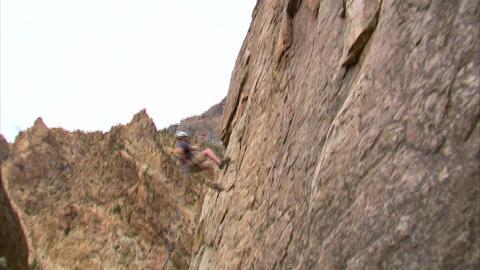 Shot of a rock climber hopping across a cliff face Live Action