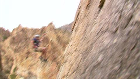 Clip of a mountain climber hopping across a cliff face Footage