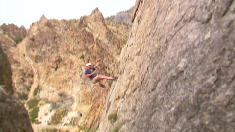 Mountain climber jumping across the face of the mountain Live Action