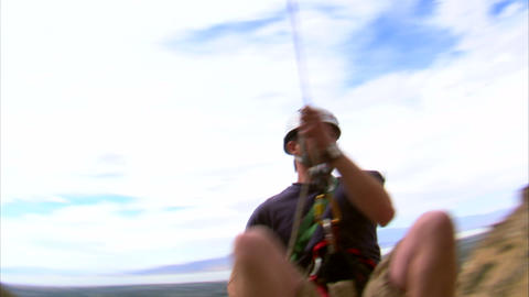 Mountain climber hopping over the camera Footage