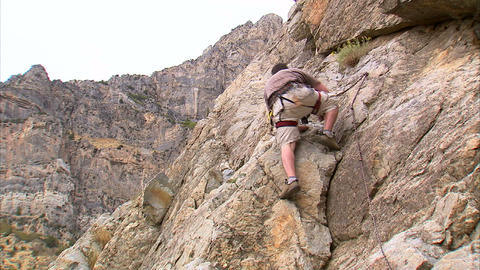 Shot of a mountain climber climbing up the face of a cliff Footage