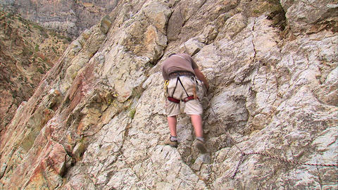 Mountain climber climbing up the face of a cliff Footage