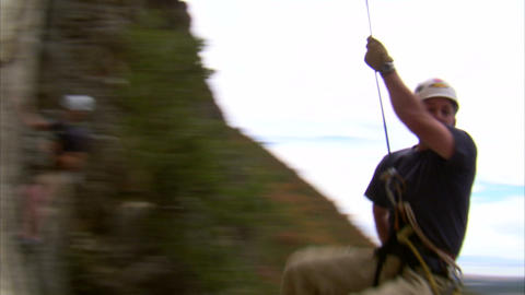 Rock climber swinging over the camera Footage