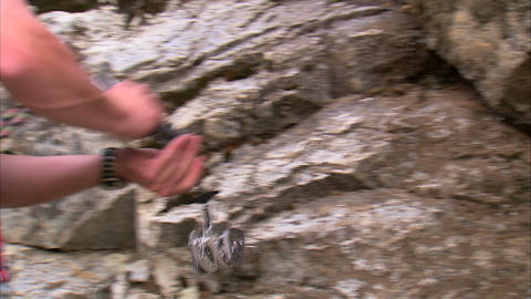 Climber taking a cam from his harness and placing it in a crack Footage