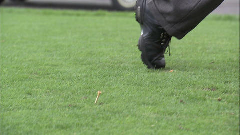 Pan of a golfer as he tees off Footage