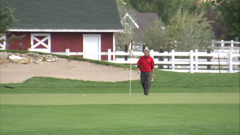 Golfer removing the pin and getting ready to putt Footage