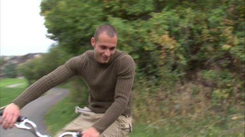 Couple riding their bikes down a path Footage