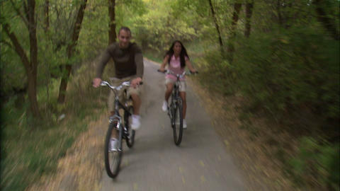 Man and woman riding their bikes down a tree-covered path Footage