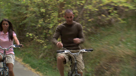 Man riding a bike with no hands with a woman Live Action