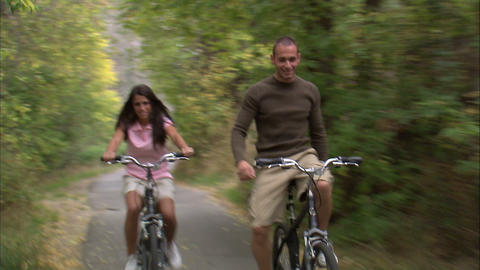 Man and woman riding bikes down a tree-covered path Footage