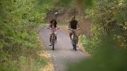 Couple riding their bikes through trees Footage