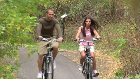 Couple riding bikes down a tree-covered path Footage