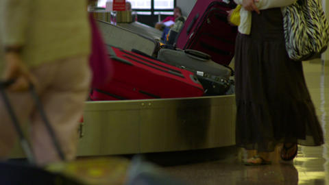 Baggage rides around on a luggage carousel as people wait for their bags Footage