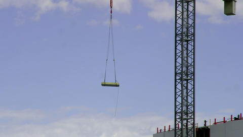 Building materials are hoisted in the air by a crane Footage