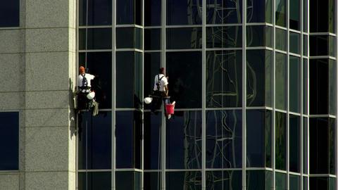 Two maintenance men washing windows in unison Footage