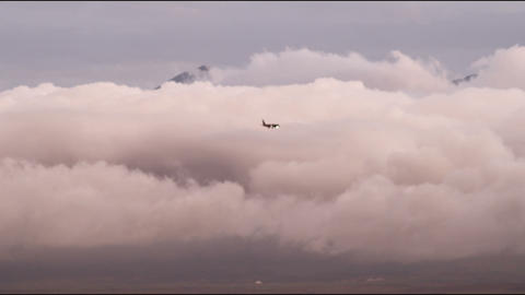 Small-looking airplane flies across a sea of clouds that mountain peak peeks ove Footage