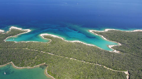 Aerial - White sand beaches with clear blue water. Boats anchored in a bay Live Action