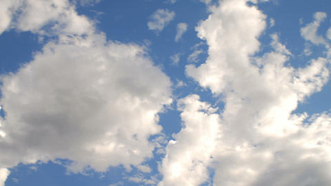 Time-lapse of fluffy clouds in a bright blue sky Live Action