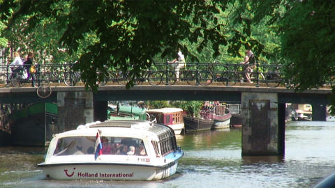 Ferry going under a bridge on a canal in Amsterdam Footage
