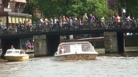 Boats on a canal going under a bridge in Amsterdam Footage