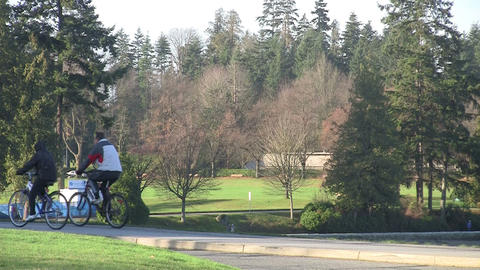 Two people on bikes in Stanley Park, Vancouver Footage