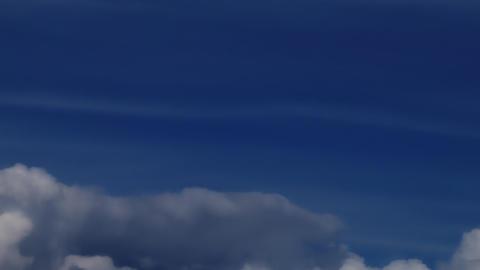 White cumulus clouds speeding furiously across an indigo sky Footage