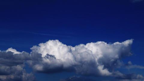 White cumulus clouds roll across an indigo sky Footage