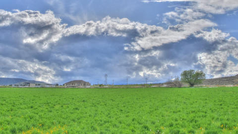 Panning time-lapse shot of thick clouds over green meadows in Utah with lens fla Footage