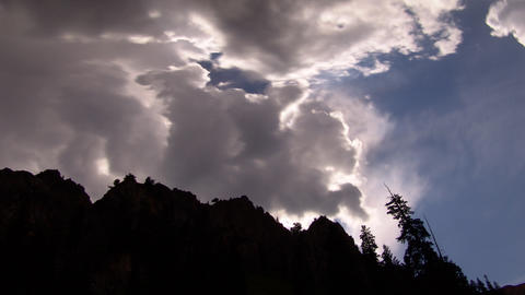 Contrasting time-lapse shot of hilltop silhouetted against the sun and sky with  Footage