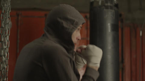 Determined kickboxing man training punches in gym Live Action