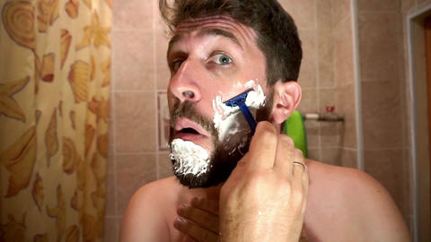 Men with beard uses a single blade safety razor to shave his beard Live Action