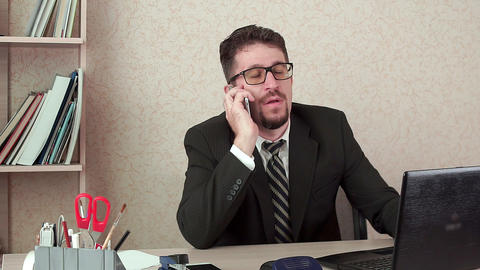 Office Manager man with beard and glasses talking happily on the smartphone Footage