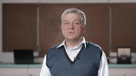 Senior teacher talking into camera as if being interviewed Live Action
