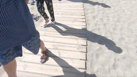 Wooden walkway on the beach with people legs passing by Footage