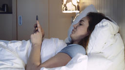 Young Woman Lying in Bed Using Smartphone Footage