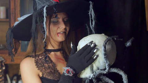 Halloween witch close-up with a staff of a human skull. Sexually smiling Footage