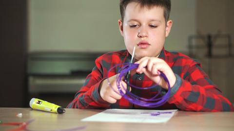 A teenager boy in a plaid shirt cuts off a piece of ABS plastic for a 3D pen Footage