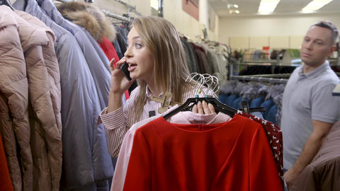 Adult happy girl emotional talking at smartphone in store about discount Footage